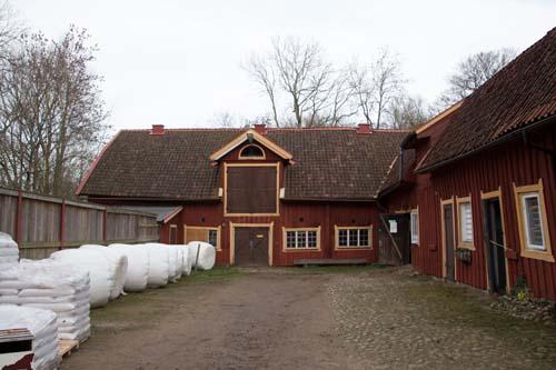 Mitt i bilden syns ingången till ladugården, troligen den bästa platsen för en utställning. Foto: Per Hallén.