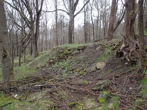 Murar för att stärka sluttningens kanter är idag de enda spåren av husen. Foto: Per Hallén 2014.