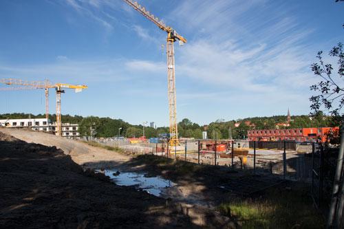 Arbetet med Posedions hus pågår på hitsidan staketet, HSB:s andra förening bortom staketet. Foto: Per Hallén 2015