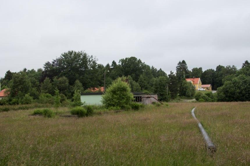 På den tidigare åkerjorden ligger en av de ledningar som skall grävas ned för den nya bebyggelsens behov. Foto: Per Hallén 2016.