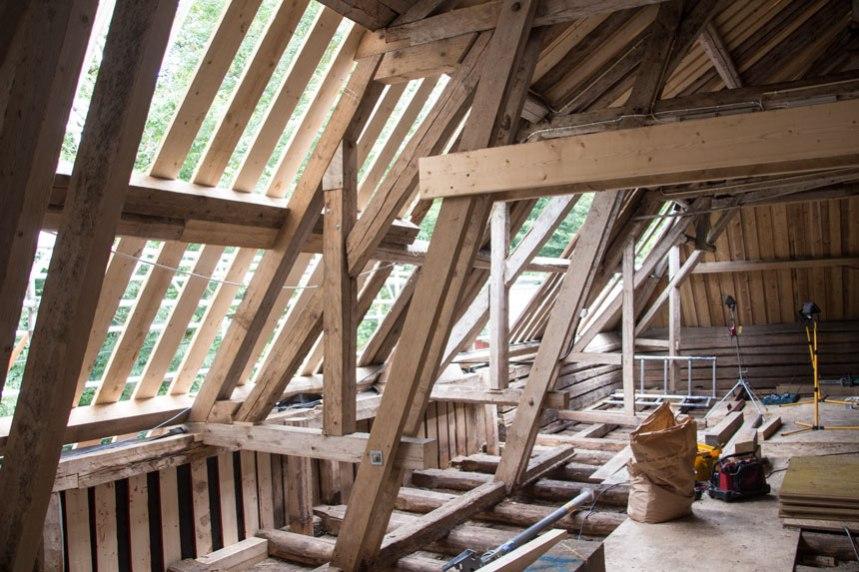 På baksidan av ladugården pågår nu arbetet med att laga taket. Foto: Per Hallén 2016